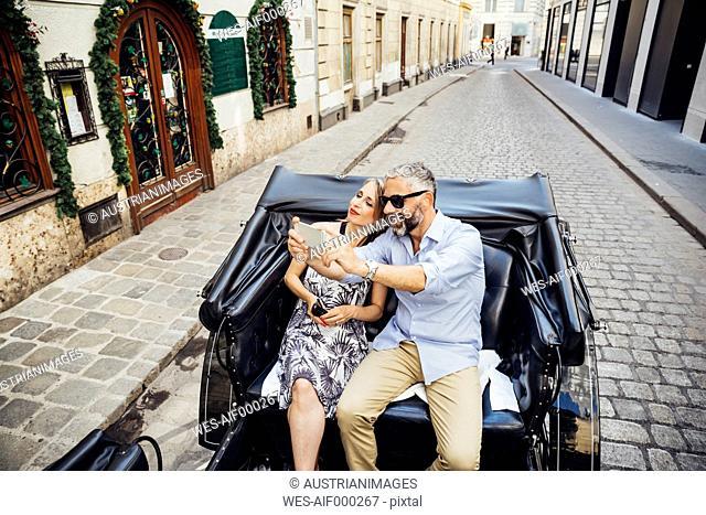 Austria, Vienna, tourists taking a selfie in a fiaker