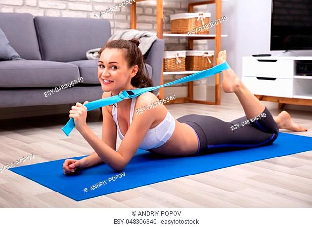 Happy Young Woman In Sportswear Doing Workout With Yoga Belt At Home