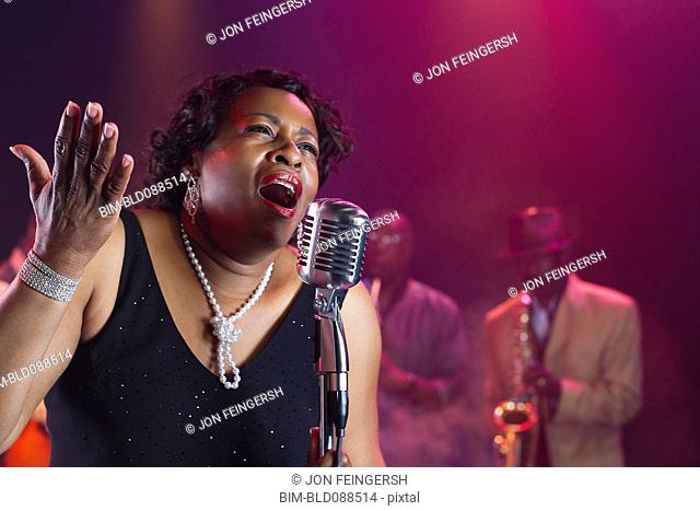 Black woman singing on stage with jazz band