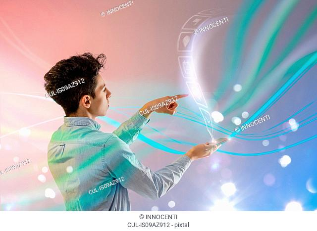 Young man using transparent touch screen
