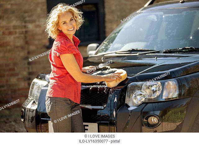 A mature woman washing a four wheel drive car
