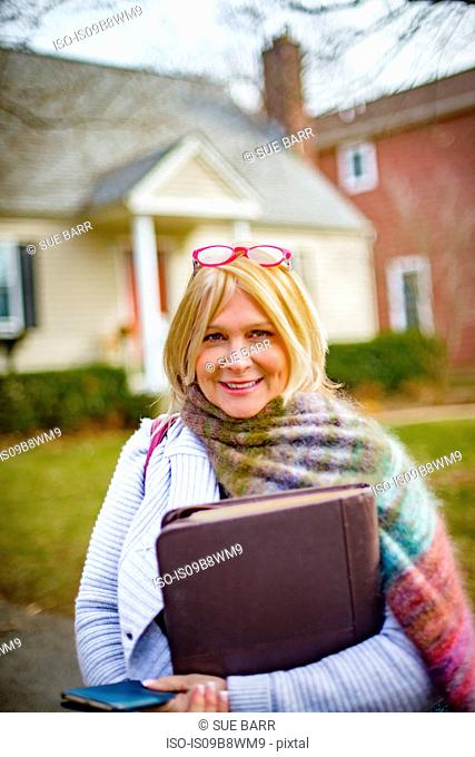 Portrait of mature woman outside house holding laptop case and smartphone