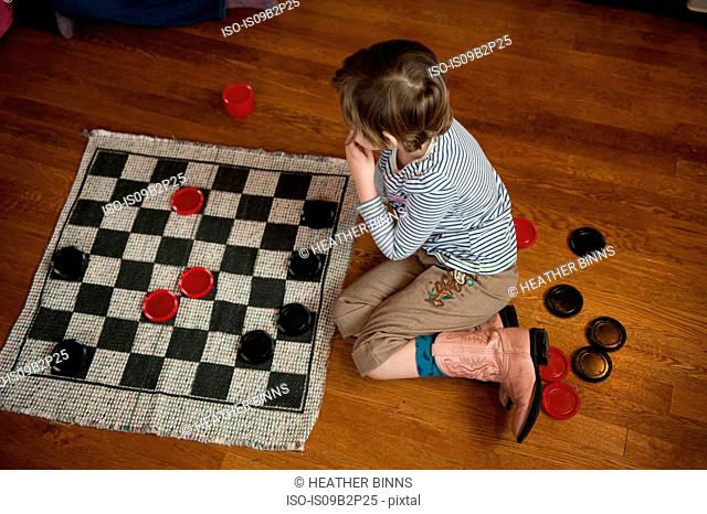 Girl sitting on wooden floor playing draughts