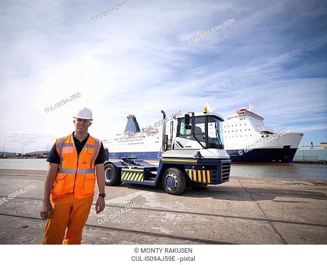 Portrait of shipping container truck driver and ship in port