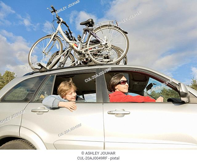 Woman & boy in car, bikes on roof