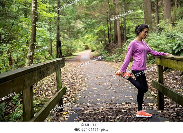 Woman stretching leg preparing for run in woods