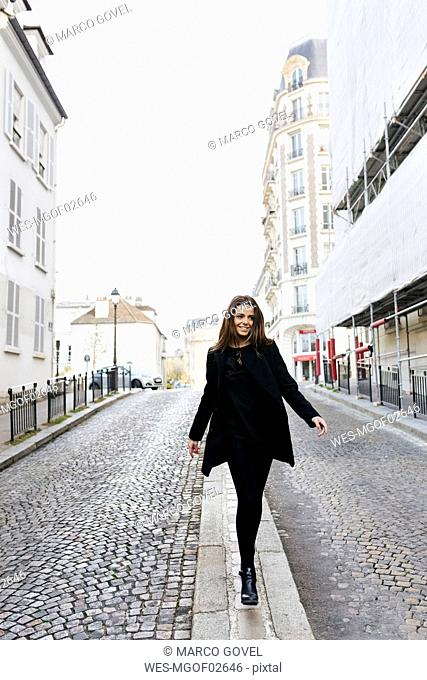 France, Paris, young woman walking on the streets of Montmartre