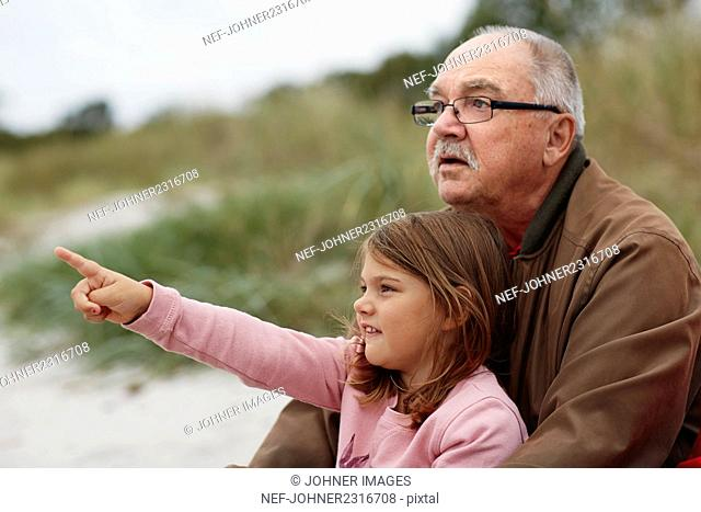 Grandfather sitting with granddaughter on beach