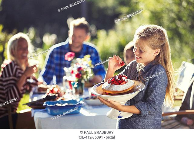 Girl holding strawberry cake at sunny garden party patio table