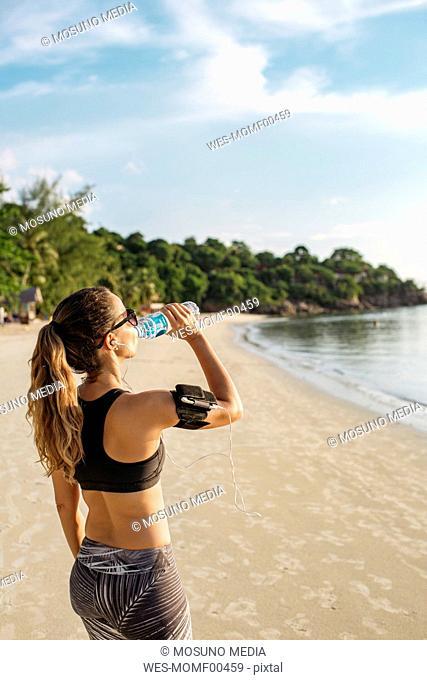 Thailand, Koh Phangan, Sportive woman drinking water on the beach