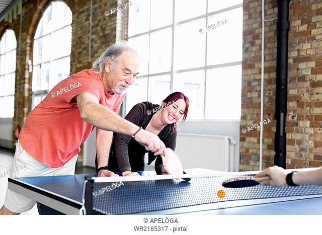 Senior man and young woman playing table tennis in health club