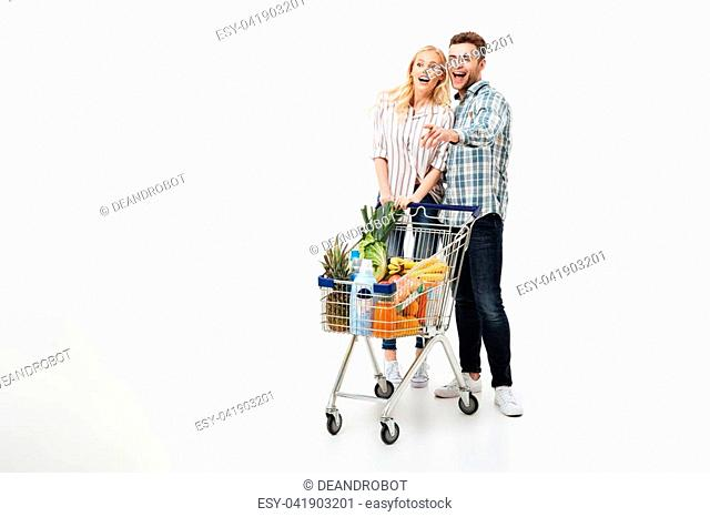 Full length portrait of a cheerful couple standing with a supermarket trolley and pointing finger away isolated over white background