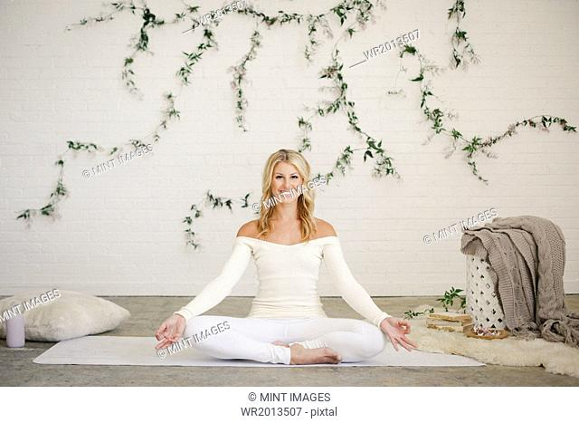 A blonde woman in a white leotard and leggings sitting on a yoga mat