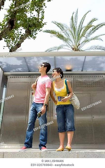 Couple waiting at bus station, smiling, low angle view