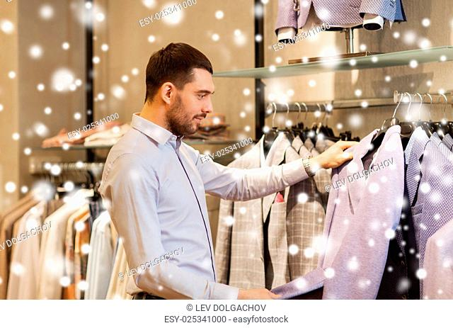 sale, shopping, fashion, style and people concept - elegant young man in shirt choosing clothes in mall or clothing store over snow