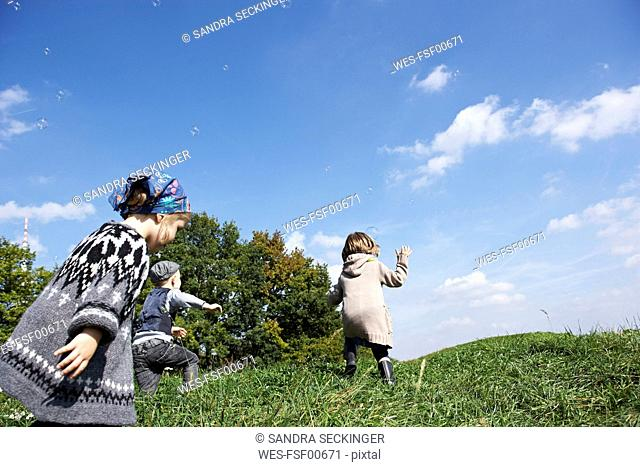 Three children playing in meadow