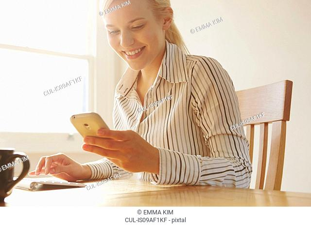 Young woman sitting at table looking at smartphone