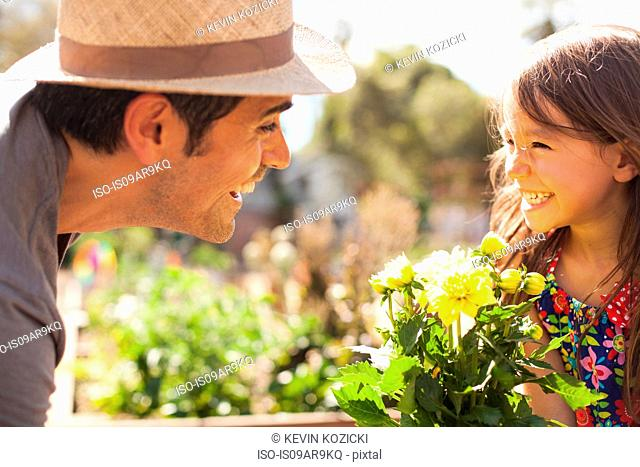 Mid adult man and daughter with yellow flower plant in community garden