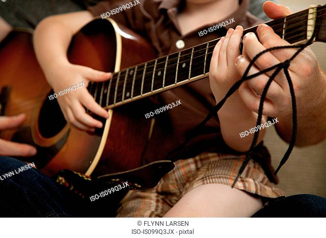 Boy and father playing guitar