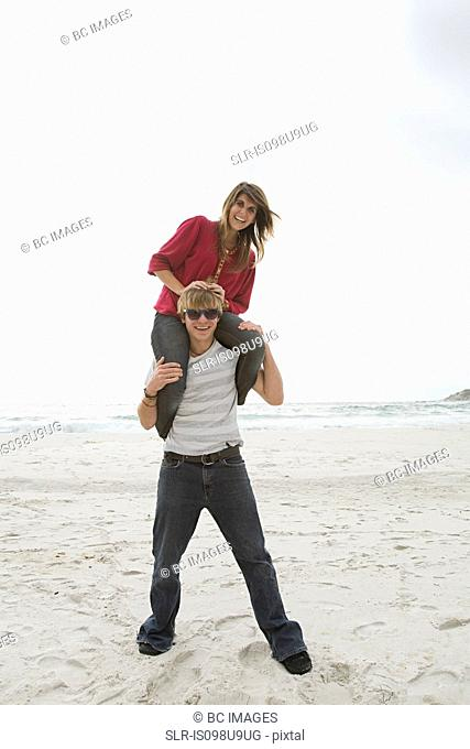 Young man carrying girl on shoulders on beach