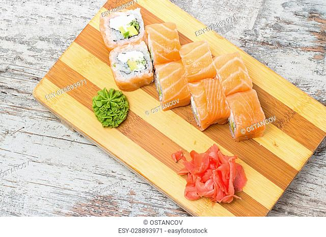 Salmon sushi roll on gete over wooden background