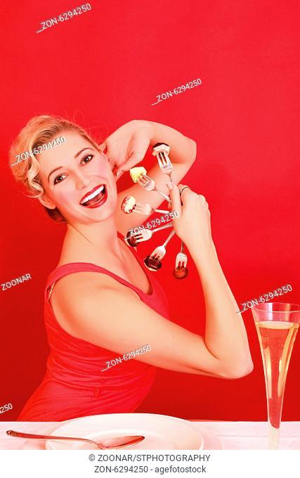 Junge Blonde Frau mit Pralinen auf Silbergabeln in Fächerform sitzend an einem gedeckten Tisch mit einem Glas Sekt.Young Blonde Woman with chocolates on silver...