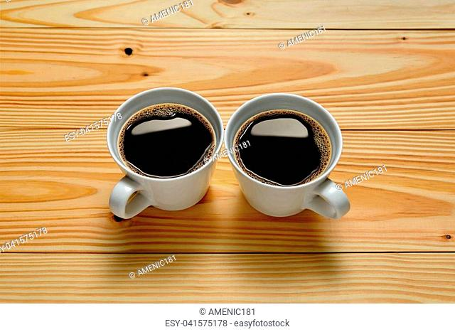 Top view of two cups of coffee on wooden background