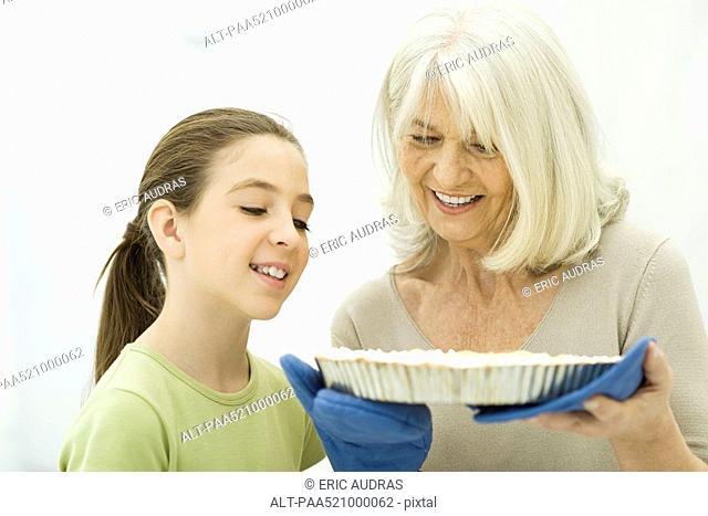 Grandmother and granddaughter looking down at freshly baked pie