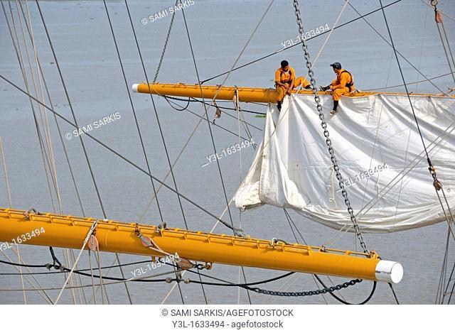 Men repairing a sail of the three-masted sailboat on Guayas river, used as a training ship for Ecuadorian Navy cadets, Guayaquil, Ecuador