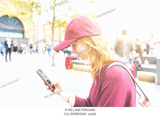 Woman in urban area using smartphone smiling, London, UK