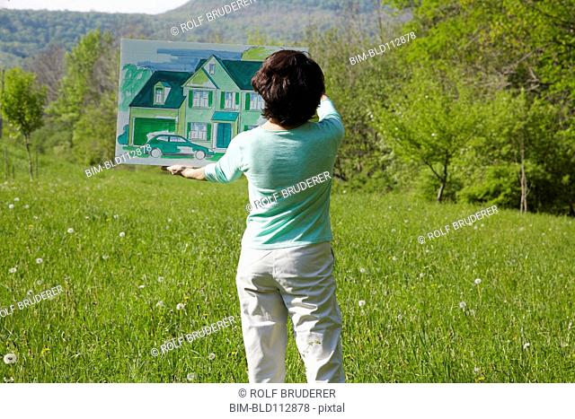 Caucasian woman visualizing house in rural landscape
