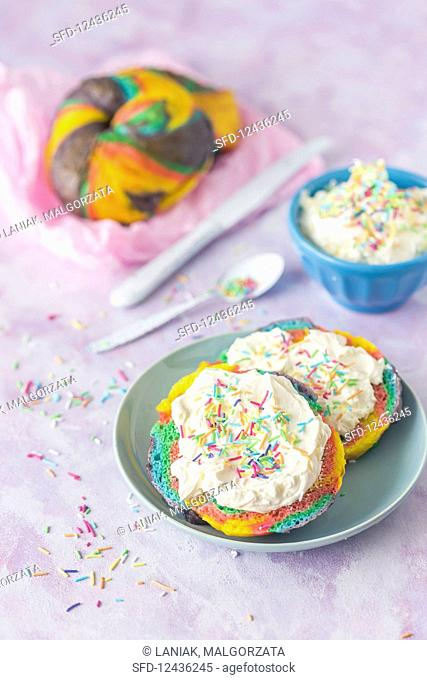 Rainbow bagels with vanilla cream and colorful sugar sprinkles