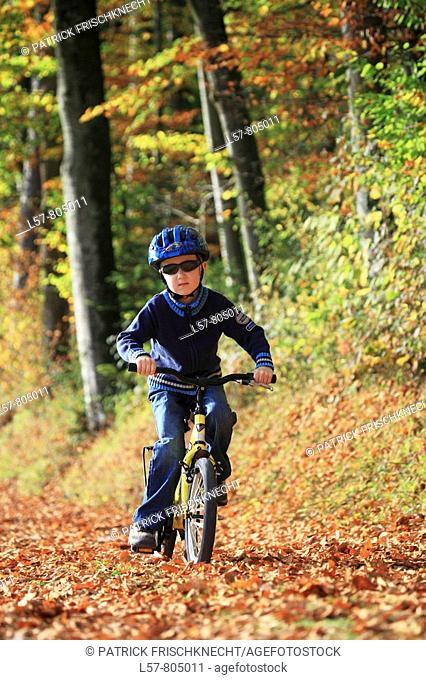 boy riding his bicycle on road with leaves in fall, autumn foliage covering path in forest, autumn, fall, Zuerich, Switzerland