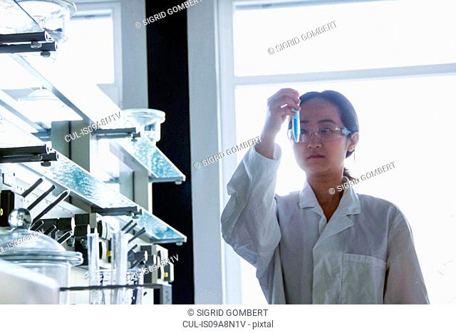 Female scientist looking at test tube