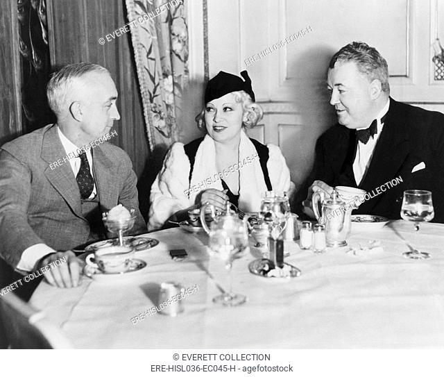 Mae West dining at the Victor Hugo CafÚ with her manager James Timony (right). At left is John Hammel of New York. 1933. (BSLOC-2013-9-13)