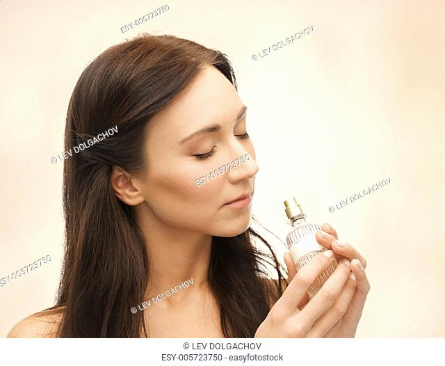 picture of young beautiful woman smelling perfume