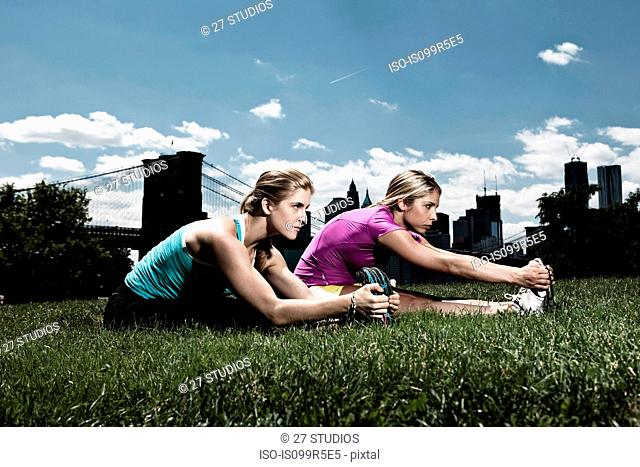 Two women stretching in park