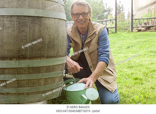 senior man filling can with rain barrel water