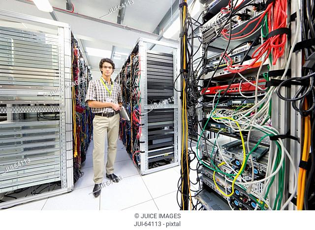 Technician, looking at camera, holding laptop computer in Server room of data center