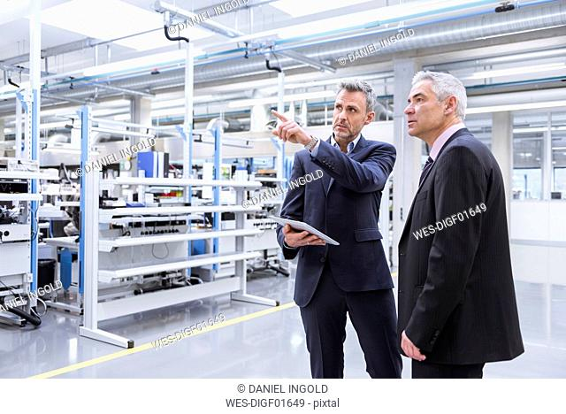 Two mangagers having a meeting at the shop floor of a factory