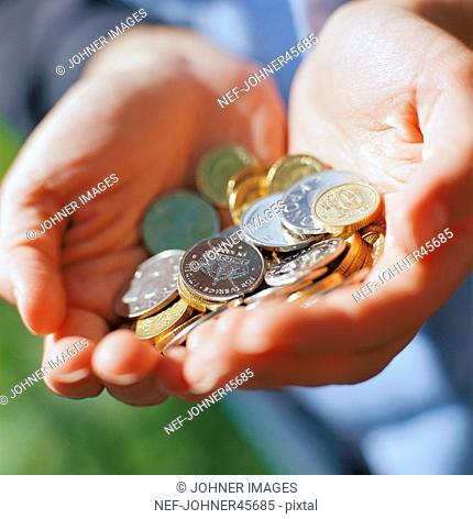Closeup of coins stored in hands