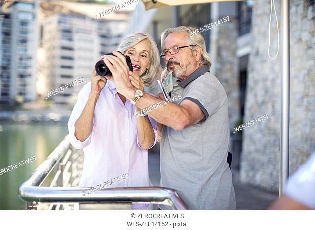 Senior couple taking a city break, taking photos
