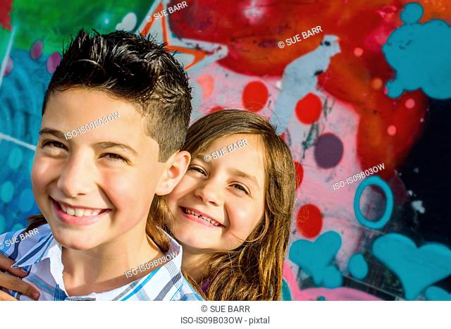Portrait of boy and sister in front of wall mural at amusement park