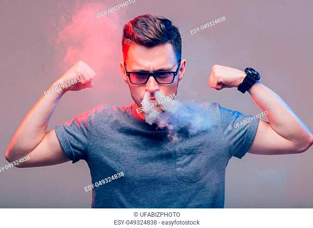 Men with beard in sunglasses vaping and releases a cloud of vapor in nose