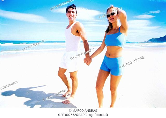 a couple walking on the beach shore