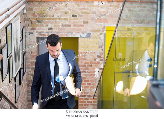Young businessman in a suit carrying longboard, climbing stairs