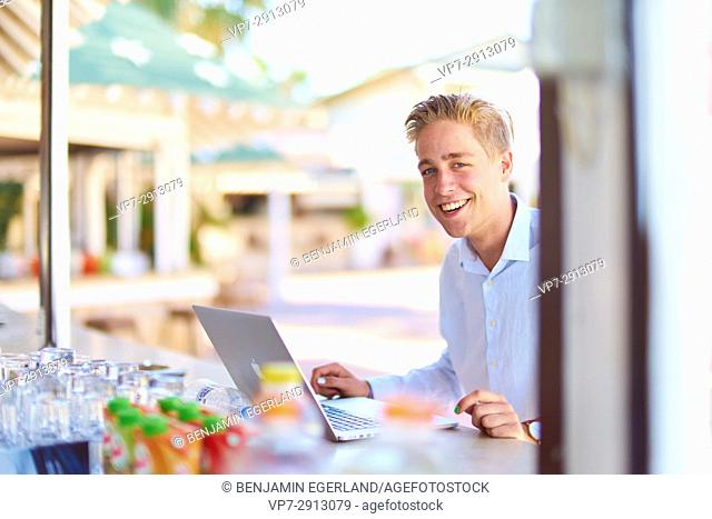 young business man with laptop computer sitting at bar