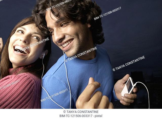 Hispanic couple listening to same mp3 player