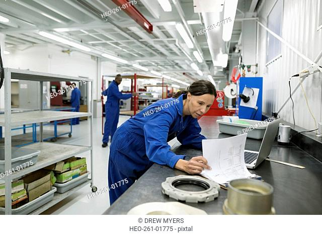 Female helicopter mechanic reviewing paperwork at workbench