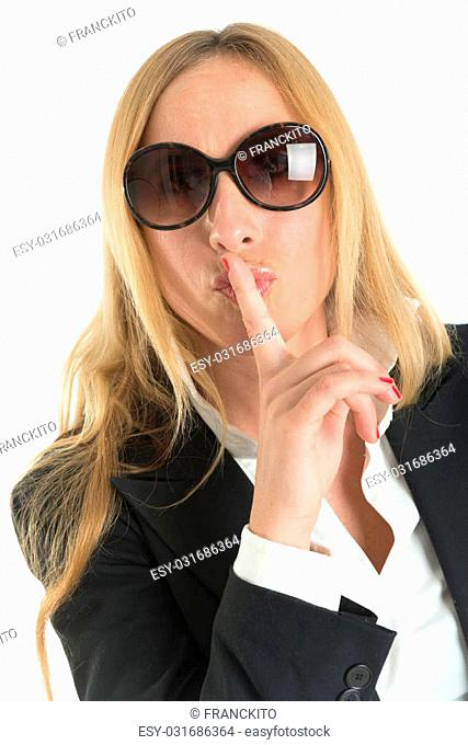 Woman with sunglasses doing a hushing gesture